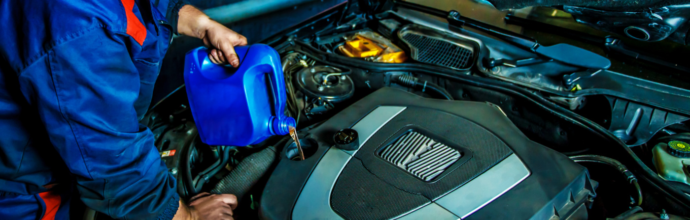 Mechanic pouring in engine oil - Car Servicing Ashby